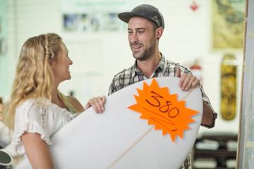 Shop assistant showing client surfboard prices