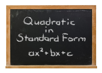 Quadratic equation in standard form written in white chalk on a black chalkboard isolated on white