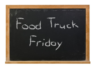 Food Truck Friday written in white chalk on a black chalkboard isolated on white