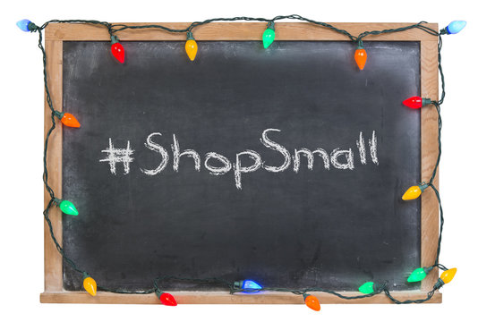 Hashtag shop small written in white chalk on a black chalkboard surrounded with festive colorful lights  isolated on white