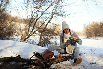Woman pouring tea from a thermos, outdoors, natural snow background, forest