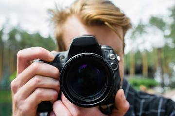 Portrait of a photographer covering his face with the camera