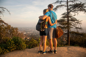 Man and woman outdoors, wearing sports clothing, standing on mountain, looking at view, rear view
