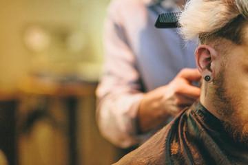 Man having hair cut in barbers, close-up