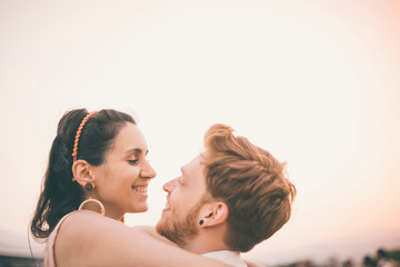 Portrait of man and woman, outdoors, face to face, hugging