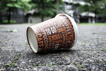 Weggeworfener leerer Kaffeebecher liegt auf Gehweg.