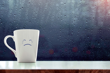 Sadness Coffee Mug with crying face cartoon inside the room, Blurred light and rain drop as outside view through glass window, Feeling blue or bad on rainy day concept