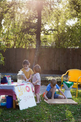 Boy and two young sisters preparing lemonade stand in garden