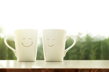 Couple of Happy Coffee Mug with smiley face in the morning, Blurred Green Natural as background, Happiness Love Concept