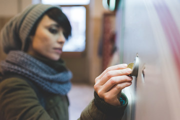 Woman inserting coin into railway ticket machine