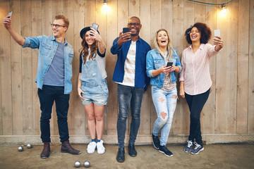 Multiethnic cheerful friends taking selfieat wooden wall