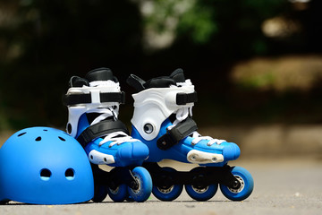 Roller inline skates with helmet in skate park on gray asphalt background
