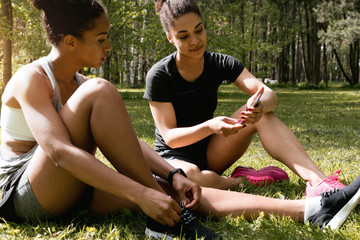 Two joggers having break after exercising in park