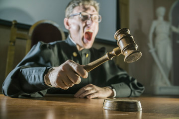 angry man a judge with a hammer in his hand in the court room