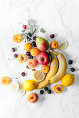 Summer fruits assorted on white marble background. Fresh raw food concept. Copy space