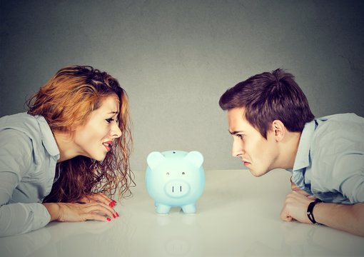 Finances in divorce concept. Wife and husband can not make settlement looking at piggy bank sitting at table looking at each other with hatred