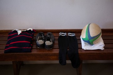 Clothes and rugby ball on wooden bench