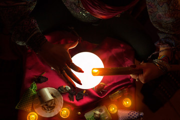 Burning candle above crystal ball