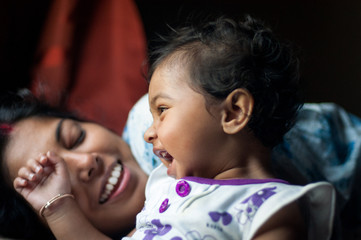 Baby girl sharing cheerful moment with her mother