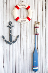 Life preserver, anchor and paddle on the white wall