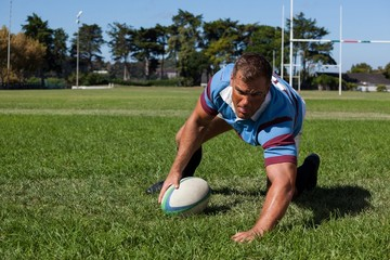 Player holding ball while playing rugby on field