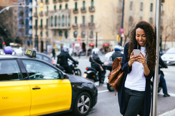 Young african american woman using her smart phone at the bus stop