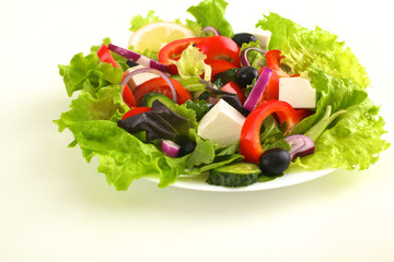 Salad of fresh vegetables and herbs on the table in the plate