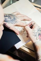 Tatooed man working on new tattoo
