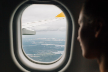 Woman looking through an airplane window