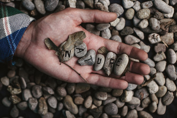 Stones background with nature word on a hand