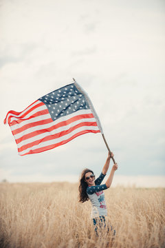Woman waving American flag while standing in a field against sky