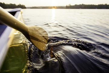 Stern of Canoe and Paddle Swirl In Lake Water At Sunset