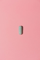 Pill on pink background from above