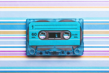 Blue cassette tape on striped and colored background