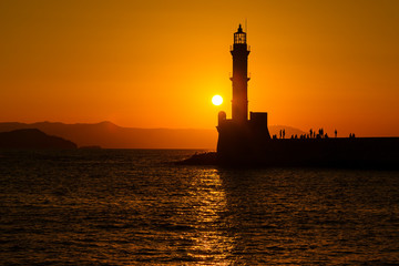Silhouette of lighthouse in sea at sunset in the city of Chania, island of Crete, Greece. Beautiful seascape at sunset