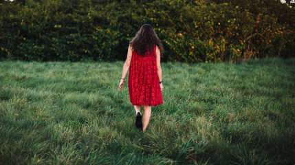 Brunette woman in red dress walks towards the bushes