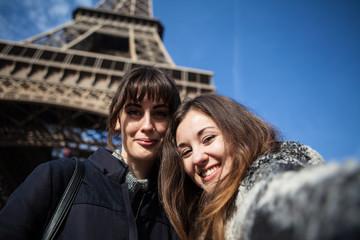 Happy young women taking a selfie under the Eiffel tower, Paris