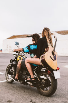 Man and woman riding a motorbike with a guitar