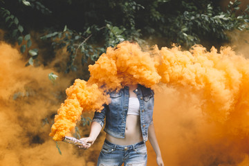 Young woman with orange smoke bomb at the nature