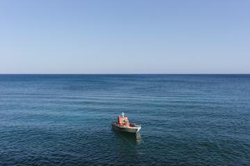 A boat in calm blue mediterranean sea against sky