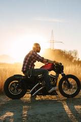 wild, young and free - casual bearded guy sitting on his bike on a dirty road at sunset