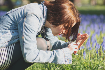 Girl taking photo of blue flowers in park