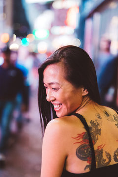Asian woman smiling in Time Square at night