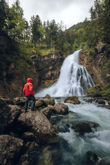 male hiker standing in front of a waterfall in the forest