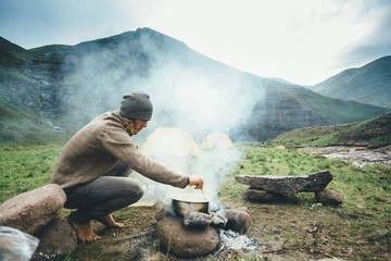 Man cooking on a camp fire at dawn