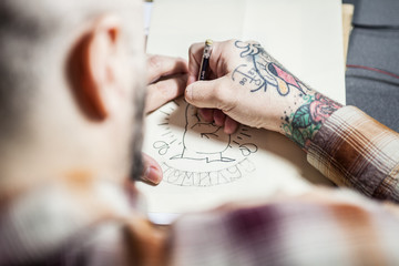 Tattoo artist drawing new tattoo sketch