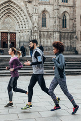 Group of young friends running in front the cathedral in Barcelona