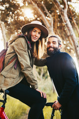 Portrait of a young couple on a bicycle in the forest