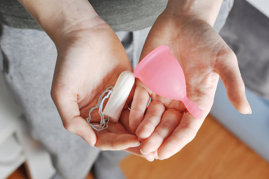 Young woman hands holding different types of feminine hygiene products - menstrual cup and tampons
