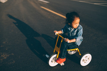 Little girl riding tricycle on road